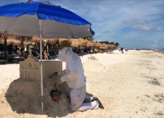 Turistas extranjeros realizan arte con arena en playas de Puerto Morelos